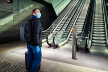 Middle-aged man in a blue face mask in rubber gloves goes on a metro platform to the escalator