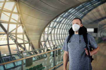 Half-length portrait of a mature man in a white medical mask walking inside of an airport building