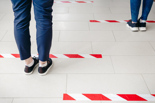 People stand in line keeping social distance, standing behind warning line during covid 19 coronavirus quarantine in store or bank. Safe shopping, Social distancing concept. Legs in line closeup