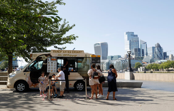People buy ice cream in Potters Field Park, with the City of London financial district in the background, in London