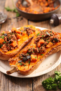 stuffed butternut squash half with minced meat and pumpkin seed