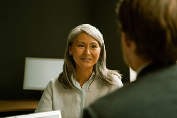 Friendly charming business woman communicates with businessman sitting with his back in foreground....