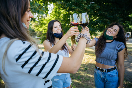 Young millennial women toasting in a park with red wine glasses in a tasting - Group of people having fun together with face mask lowered in protection by Corona virus, Covid-19