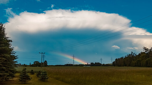 Beautiful rainbow with powerlines and a big storm cloud near Tabertshausen, Bavaria, Germany