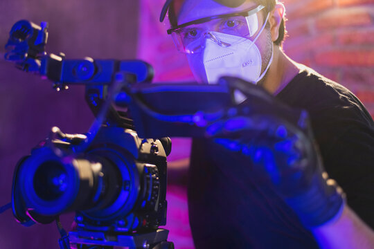 Photographer wearing kn95 mask with a professional camera Behind the scenes of video production,  coronavirus protection concept