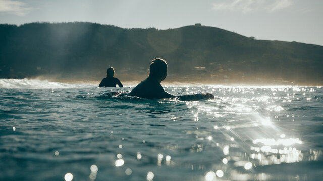 two surfer girls talking in the sea