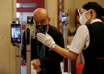 Staff members conduct a simulation for body temperature checks and hand sanitizing at the entrance of the Kabukiza Theatre amid the coronavirus disease (COVID-19) outbreak in Tokyo