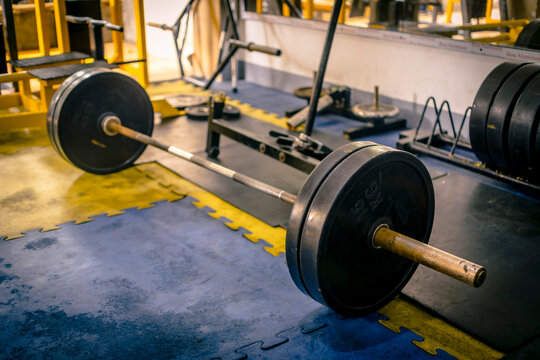 A rusty olympic size barbell loaded with plates on rubber matting. In position for deadlift. hardcore theme and setting.