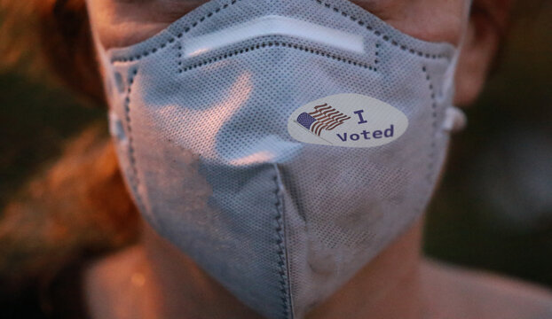 I Voted sticker with USA flag on face mask on caucasian female after voting for president for President