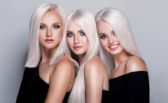 Three beautiful girls with hair coloring in blond. Straight and smooth hair coloring in ultra blond color in a beauty salon. Beauty, cosmetics and makeup