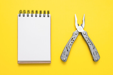 Blank paper page notepad and steel multi tool on the yellow flat lay background.