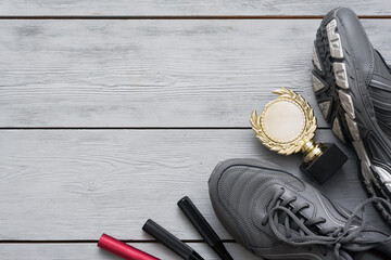 Sport shoes and golden award trophy on the wooden flat lay floor background with copy space.