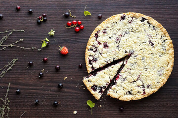 Homemade shortbread berry pie with a slice cut off on wooden table texture. Summer photo receipts