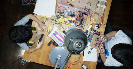 Top view, young Asian kids busy making DIY robotic project on messy wooden table full of electronic...