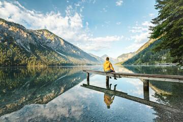 Frau sitzt am See in den Bergen