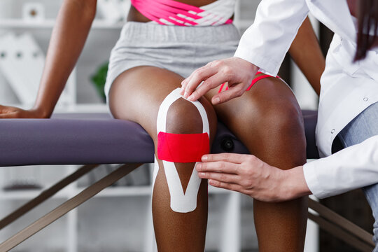 Physiotherapist applying kinesiology tape to patient knee.Therapist treating young female African American athlete. Kinesiology taping. Post traumatic rehabilitation,sport physical therapy.
