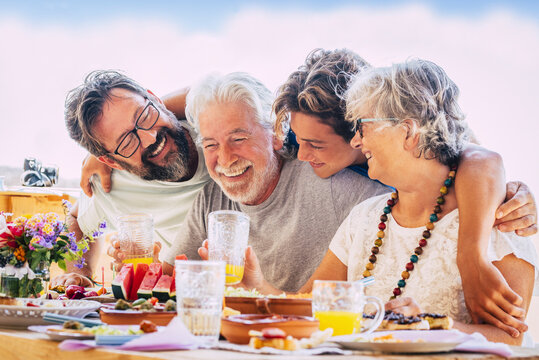 Family caucasian people hug and enjoy celebration together - mixed ages with teeanger, adult and senior people having lunch and fun - son, father and grandfathers laugh and eat at home