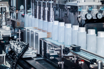 white plastic bottle moving on conveyor belt of auto capping and labeling machine at cosmetic and...