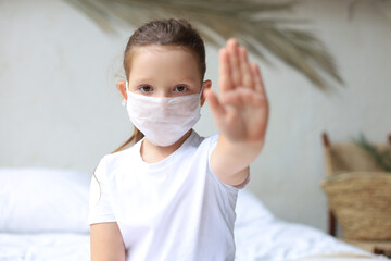 Little girl in medical masks showing Stop of COVID-19 epidemic.