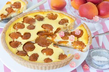 Aprikosentarte auf Tortenplatte und frische Aprikosen
