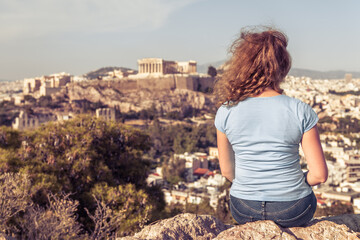 Fototapete - Adult pretty girl tourist relaxes on hilltop overlooking Acropolis of Athens, Greece