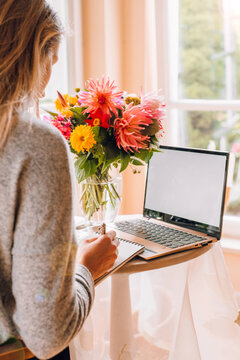 woman working on laptop at home in light vintage interior