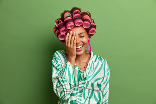 Happy dark skinned woman makes face palm, cannot stop laughing after hearing joke, expresses positive emotions, wears hair curlers to look fabulous at tomorrow party, dressed in silk gown. Hairstyling