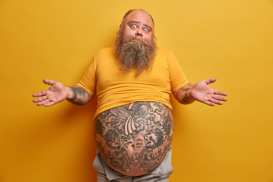Hesitant thick man with big tattooed belly, shrugs shoulders and looks confused, faces dilemma, makes serious decision, wears undersized yellow t shirt, poses indoor. People and doubt concept