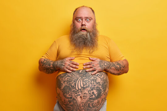 Shocked amazed hipster man keeps hands on belly with tattoo sticking out from t shirt, surprised to find out his weight, has long thick beard, poses against yellow background. Guy shows big abdomen