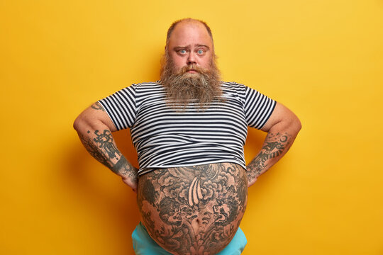 Confident serious blue eyed man with beard, has big abdomen, leads unhealthy lifestyle, dressed in striped undersized sailor t shirt, poses over yellow background. Plump guy stands self assured indoor