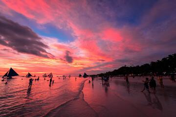 フィリピン・ボラカイ島のホワイトビーチにて、赤く染まる夕焼け空を眺める