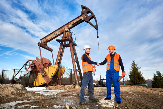 Two men wearing overalls, orange vests, and helmets, standing on oil field next to oil pump jack shaking hands, blue sky on background. Concept of business, petroleum industry and oil extraction.