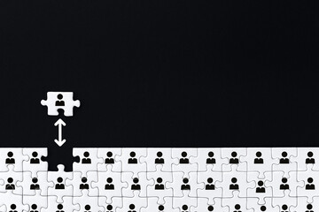 White gray puzzles with depicted man icon symbol are stacked on bottom of black background. One piece located separately on distance. Concept of rejection, inequality, discrimination. Introvert person