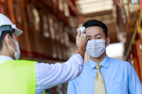 Businessman has temperature check at warehouse industry before enter to the workplace, pandemic protective system, new normal employment.