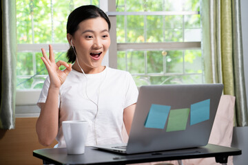 Asian woman with earphone happy video call with laptop sitting on the bed and showing OK sign at...