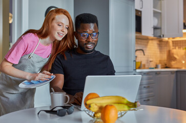 interracial couple spend time in the kitchen at home, african man work on laptop, redhead female look how he is working