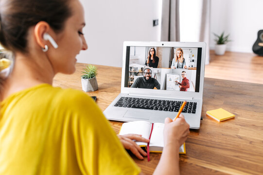 Back view of laptop display with a group of multiracial people on it, young woman watching online webinar and writing notes. Video call, online conference