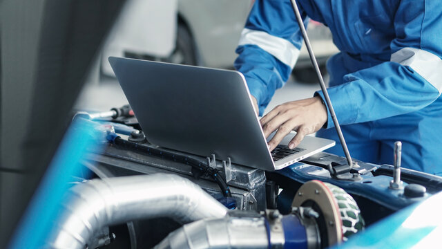 Mechanic using laptop computer working tuning on car for the efficiency of the race car in garage.maintenance concept
