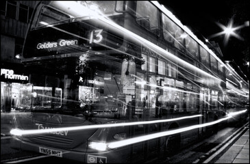London, UK – Oct 6, 2011: Black & white image of a No 13 red double decker bus at night passing through Oxford Street with light trails