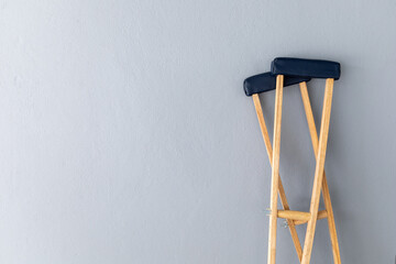 closeup pair wooden crutches on gray background