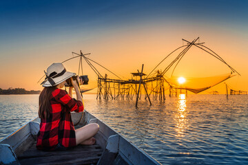 Wall Mural - Woman traveler take a photo to fishing dip nets at Pakpra in Phatthalung, Thailand.