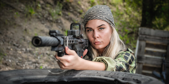 Beautiful and attractive woman soldier shooting with rifle machine gun from behind and around cover or barricade. Female  army military combat training on the shooting range