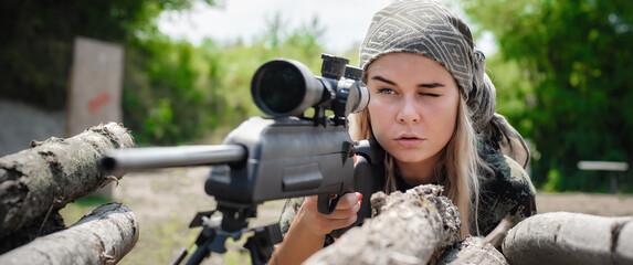 Female soldier shooting with sniper rifle. Woman with weapon. Firearm army shooting and tactical training. Outdoor shooting range