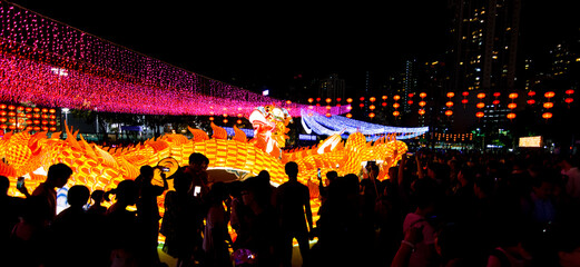 Night shot of scenic Mid-Autumn Festival with fire dragon and large crowd in Hong Kong