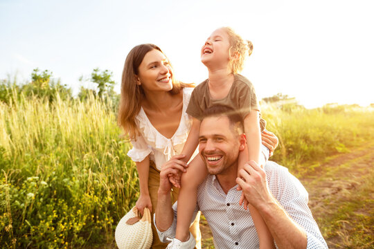 Happy parents and kid walking together in summer