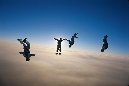 skydiving group of people above the clouds