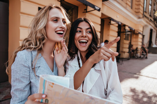 Outdoor photo of two girls enjoying sightseeing. Gorgeous female tourists exploring city with map.