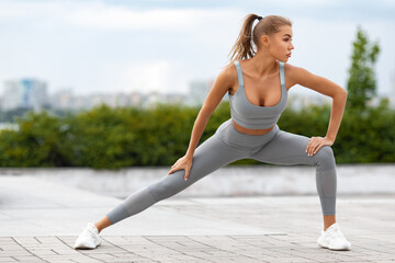 Fitness woman stretching and warming up for her training outdoors. Active girl doing lunges exercises