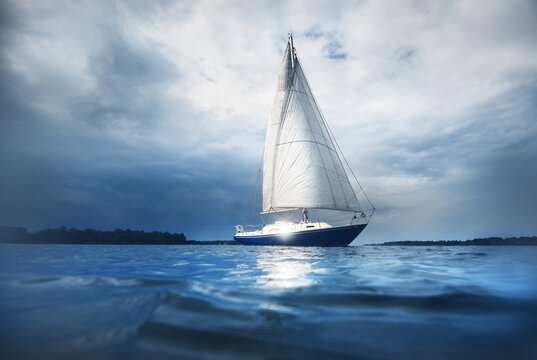 Blue sloop rigged yacht sailing in an open Baltic sea, close-up. Dramatic sky. Riga bay, Latvia. Cruise, sport, recreation, leisure activity concepts