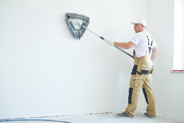 Painter works with triangle drywall cleaning tool. Surface preparation for painting